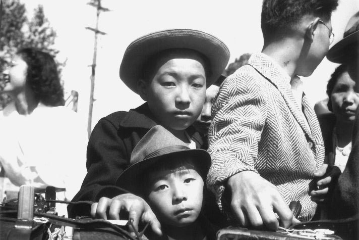"""Dorothea Lange, """"Young evacuees of Japanese ancestry wait their turn for baggage inspection, Turlock, CA,"""" 1942 [detail]. Gelatin silver print (printed later). Private collection; courtesy of Photographic Traveling Exhibitions."""
